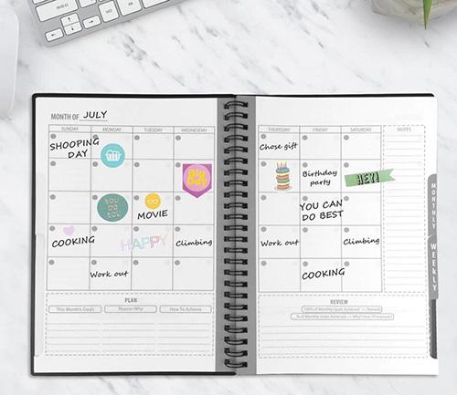 Cahier réutilisable agenda format A5 avec planificateur sur table en marbre avec ordinateur et plante