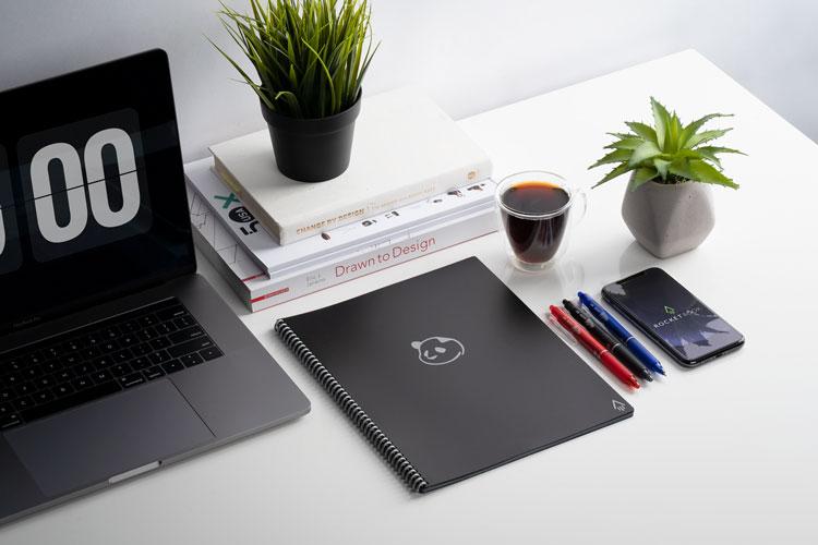 Cahier réutilisable rocketbook panda planner sur table avec ordinateur, téléphone et plante