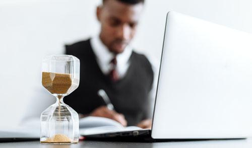 Homme en train d'écrire dans un cahier devant un ordinateur et sablier
