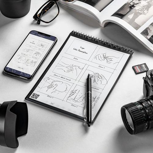 cahier réutilisable à côté d'un téléphone, d'un livre et d'un appareil photo