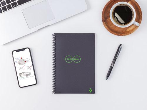 Cahier intelligent effaçable sur une table blanche avec ordinateur, ordinateur, café et stylo