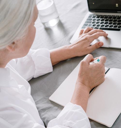 grand-mère en train d'écrire dans un cahier réutilisable