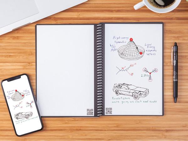 cahier réutilisable avec téléphone et stylo FriXion, posés sur une table en bois