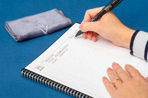 Cahier réutilisable Fusion avec main en train d'écrire sur table bleue