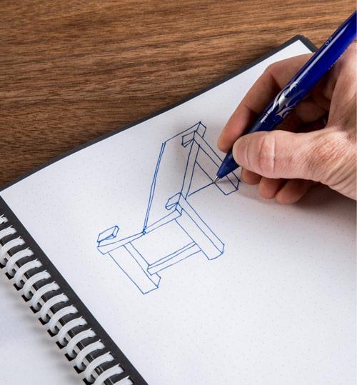 Main en train d'écrire sur cahier réutilisable rocketbook wave avec un stylo pilot FriXion