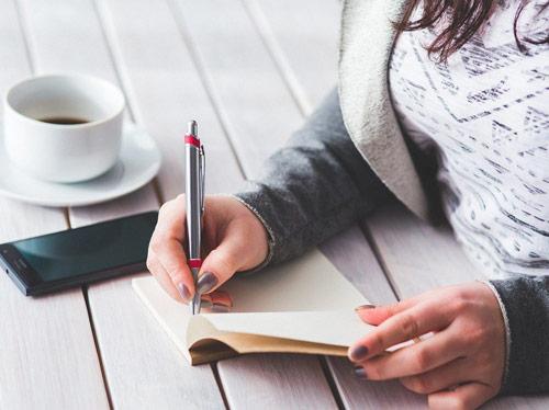 femme en train d'écrire dans un cahier sur une table avec café et téléphone