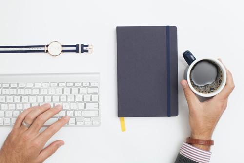Main gauche sur clavier et main droite avec café à côté d'un cahier