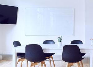 salle avec tableau blanc, chaises bleues et table