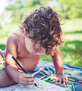 Enfant bas âge en train de dessiner dans un cahier avec crayon à l'extérieur