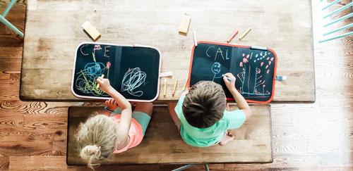 Cahiers ardoises Jaq Jaq Bird avec enfants en train de dessiner sur table